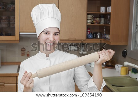 portrait of a chef holding a pan and smiling while looking at the camera
