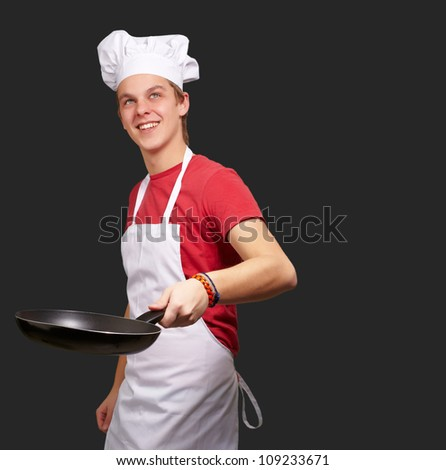 Portrait Of A Chef Holding Pan On Black Background