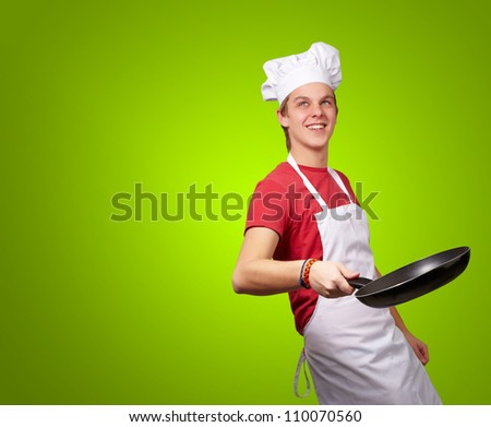 Portrait Of A Chef Holding Pan On Green Background - stock photo