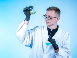 Portrait of a chemist with two test tubes in his hands. He looks at one of them. Young scientist chemist. Chemist student is engaged in national research. Chemical laboratory employee.
