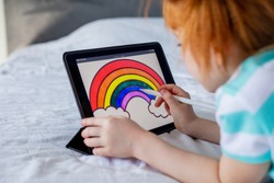 portrait of a child a girl with red hair draws a rainbow on a tablet