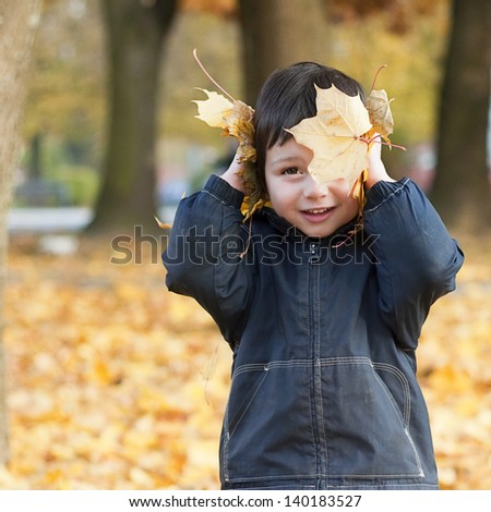 Portrait of a child boy playing in a park with yellow autumn or fall leaves.