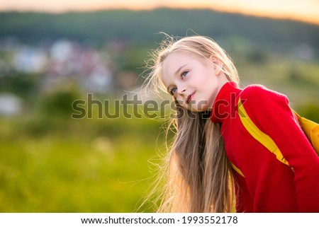 portrait of a child girl in a red jumper with a backpack traveling on a summer evening against the backdrop of a landscape.