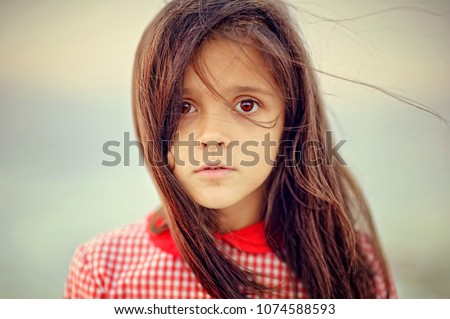 Portrait of a child girl with sad expression. Hopeful concept