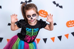Portrait of a child girl with sugar skull makeup in a costume of skeleton over white background with bats and pumpkin.