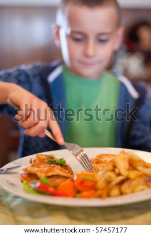 Portrait of a child having lunch in a restaurant