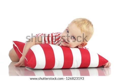 Portrait of a child lying on soft pillow studio shot