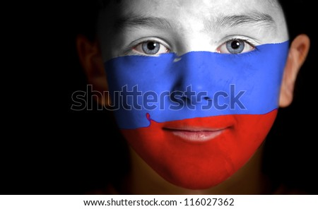 Portrait of a child with a painted Russian flag, closeup