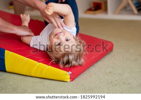 Portrait of a child with cerebral palsy on physiotherapy in a children therapy center. Boy with disability has therapy by doing exercises. Special needs kid has therapy with physiotherapist.