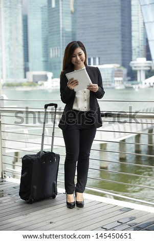 Portrait of a Chinese Businesswoman with suitcase using digital tablet
