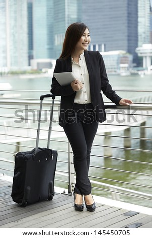 Portrait of a Chinese Businesswoman with suitcase using digital tablet.