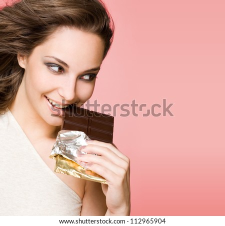Portrait of a chocolate loving brunette beauty on pink background.