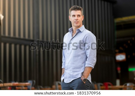 Portrait of a classy and successful businessman wearing a blue elegant shirt and standing with the hands in the pocket. Urban decay with black container in the background. Young entrepreneur Photo stock ©
