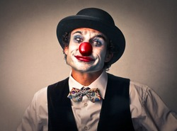 portrait of a clown with red nose and bowler hat