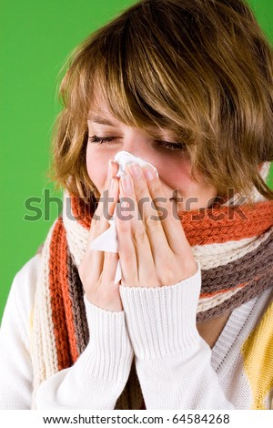 portrait of a cold girl sneezes on green background - stock photo