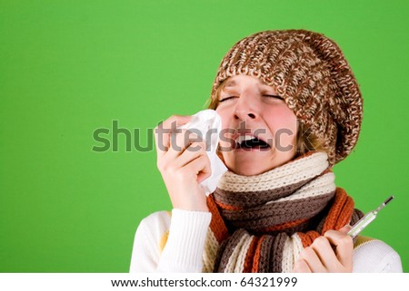 portrait of a cold girl sneezes with handkerchief and thermometer on green background