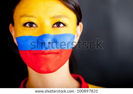 Portrait of a Colombian woman with the flag painted on her face
