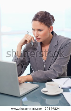 Portrait of a concentrated businesswoman using a laptop in her office