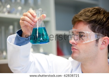 Portrait of a concentrated male scientist looking at an erlenmeyer in his laboratory