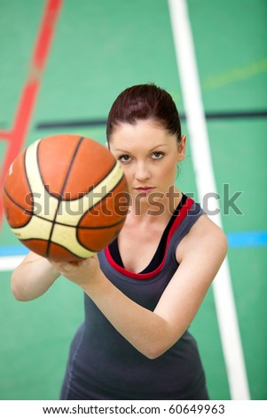 Portrait of a concentrated young woman playing basket-ball in a gymnasium
