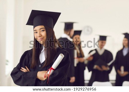 Portrait of a confident and proud Asian female student in a university graduate gown and with a diploma in her hands. Woman posing with crossed arms in classroom on the background of classmates. Сток-фото ©