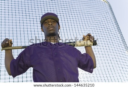 Portrait of a confident baseball player holding bat during practice against the net