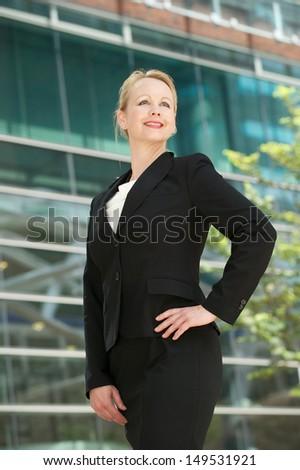 Portrait of a confident business woman smiling outside office building - stock photo
