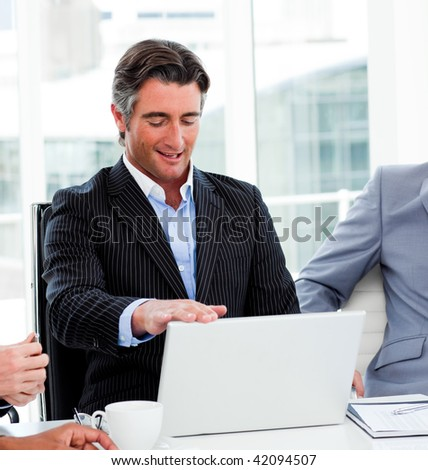 Portrait of a confident businessman using a laptop in a meeting
