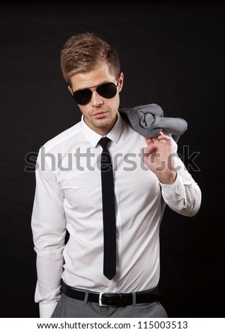 Portrait of a confident businessman wearing sunglasses on dark background