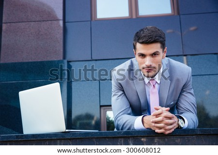 Portrait of a confident businessman with laptop computer outdoors. Looking at camera #300608012