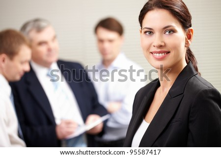 Portrait of a confident businesswoman smiling and looking at camera while his colleagues discussing a project
