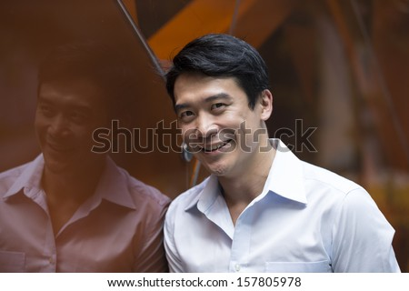 Portrait of a confident Chinese businessman standing outside in business district.