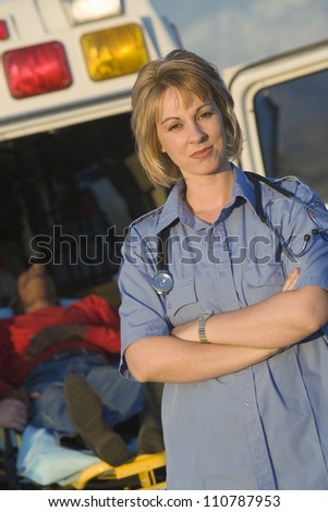 Portrait of a confident female EMT doctor standing with patient lying on stretcher in the background - stock photo