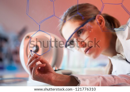 Portrait of a confident female health care professional in his working environment writing structural chemical formula on a glass board.