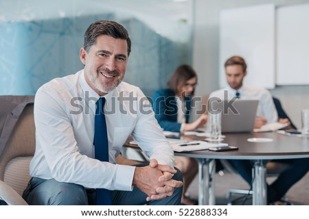 Portrait of a confident mature businessman wearing a shirt and tie sitting at a table in an office with colleagues working in the background