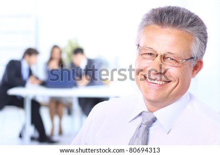 Portrait of a confident senior business man at meeting colleagues sitting at the back
