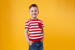 Portrait of a confident smiling little kid standing with hands in pockets isolated over orange background