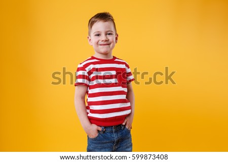 Stock Photo Portrait of a confident smiling little kid standing with hands in pockets isolated over orange background