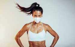 Portrait of a confident sportswoman with protective face mask. Muscular female wearing sports clothing and face mask with hands on hips against white background.