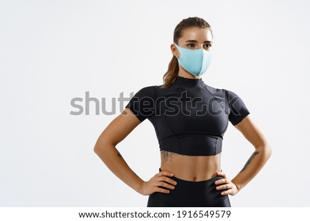 Portrait of a confident sportswoman with protective face mask. Muscular female wearing sports clothing and face mask with hands on hips against white background. Foto stock ©