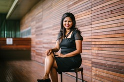 Portrait of a confident, successful and attractive Indian Asian business woman sitting on a chair in a corridor of her office in the day. She is smiling for her professional head shot for Linkedin.