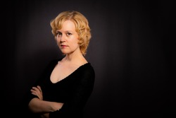 Portrait of a confident woman in her forties with short blond hair, in front of a dark background.