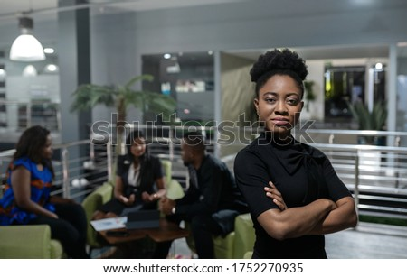 Portrait of a confident young African businesswoman standing with her arms crossed with colleagues meeting in the background