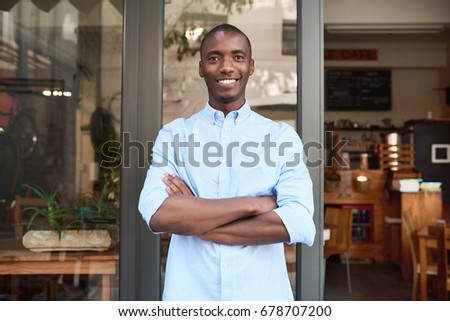 Portrait of a confident young African entrepreneur smiling while standing with his arms crossed in front of his trendy cafe