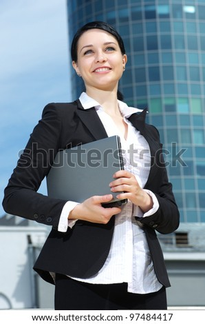 Portrait of a confident young business lady against downtown background.