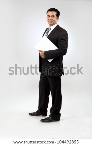 Portrait of a confident young indian business man standing with laptop