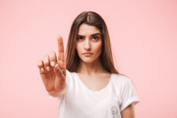Portrait of a confident young woman showing stop gesture isolated over pink background