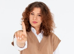 Portrait of a confident young woman showing stop gesture isolated over white background