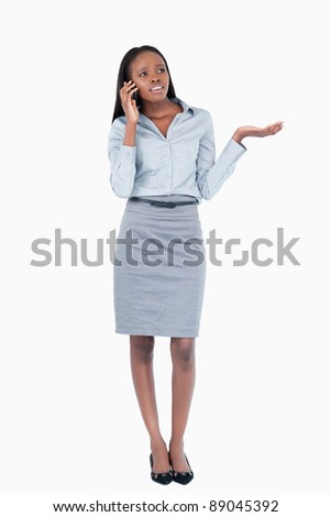 Portrait of a confused businesswoman making a phone call against a white background