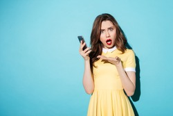 Portrait of a confused cute girl in dress pointing at mobile phone and looking at camera isolated over blue background